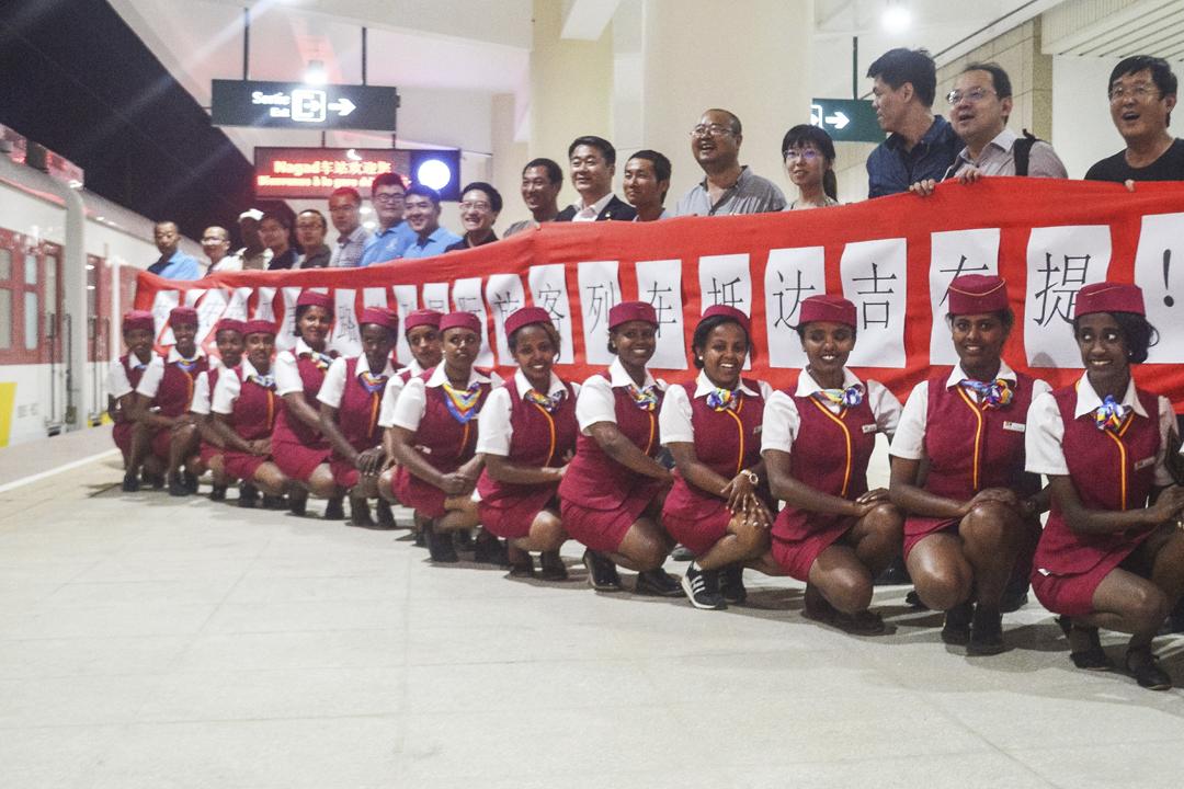中國近年積極投資非洲基建項目,以換取商業、貿易、軍事等合作,其中包括對東非國家吉布堤;去年8月,中國駐吉布堤保障基地正式啟用,為中國首個海外軍事基地。圖為今年1月3日在吉布堤市的 Nagad 鐵路站內,有中國大陸工人舉起橫額慶祝首列亞吉鐵路商務列車抵達。 攝:Houssein Hersi / Getty Images