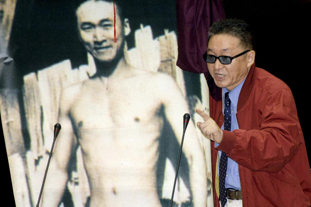 2018年3月18日,台灣作家李敖在台北榮民總醫院因病逝世,終年83歲。圖為2006年11月10日,李敖為了抗議軍購案通過,在立法院質詢時展示自己年輕時的裸照。 攝:Sam Yeh/AFP/Getty Images