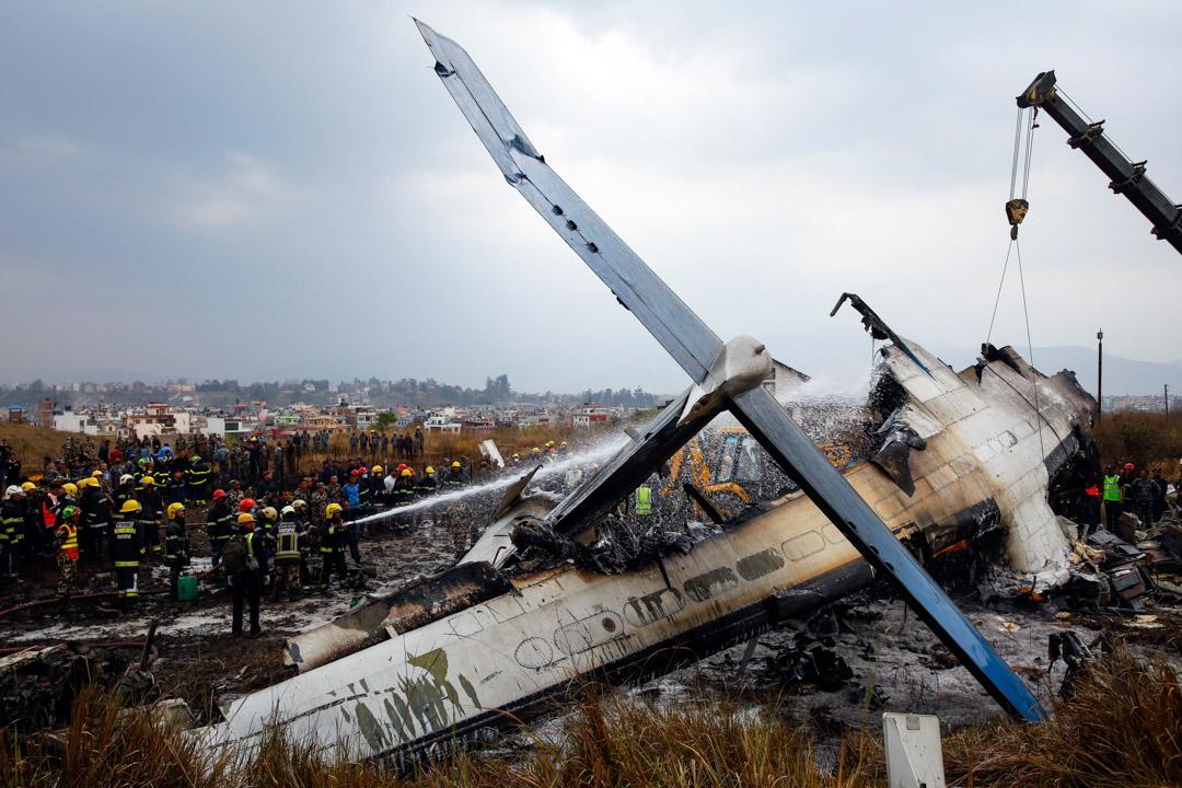 2018年3月12日,尼泊爾首都加德滿都機場,一架孟加拉 US Bangla 航空的客機於當地時間下午2時15分降落時墜毀,造成最少40人死亡,23人受傷。救援隊在現場支援,消防員向飛機射水降溫。 攝:Narendra Shrestha/EPA