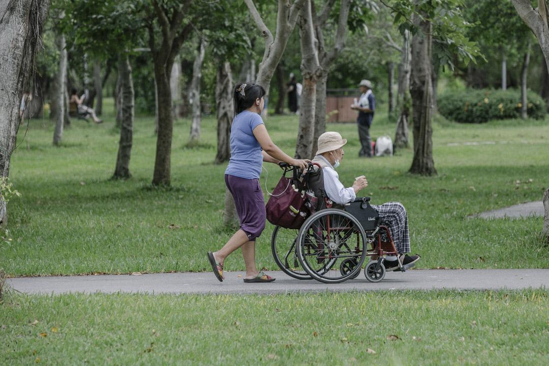 台灣子女對「照顧老人」的想像,恐怕還是「送養老院」這樣的圖像居多,但多半都會面對「不孝」的罵名,許多子女不堪指責、也不忍心與父母分離,便選擇讓外籍勞工來家照顧父母。圖為台北大安森林公園,外籍看護照顧長者。