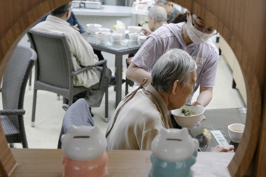 賴清德以「功德說」勉勵長者護工,點出嚴重的台灣長照問題:資源不足、實踐困難,導致行政院長必須用「做功德」來勉勵第一線工作人員,希望他們不要放棄。圖為台北市老人安養中心,看護士在午膳時間協助長者吃飯。 攝:Will Lin/端傳媒