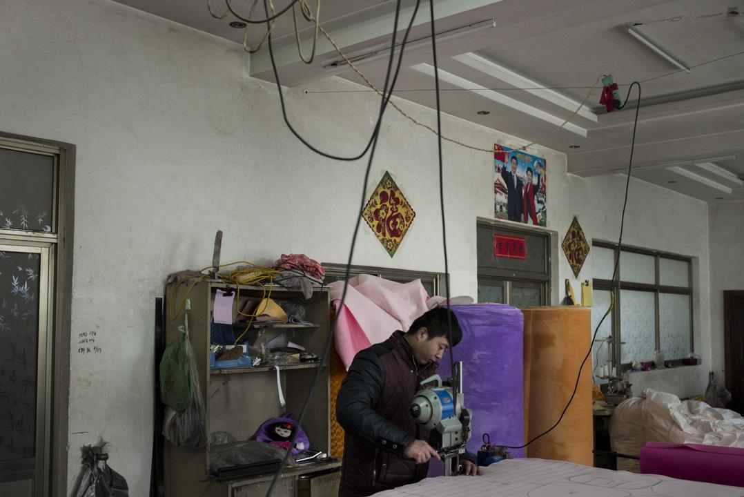 容城縣曾被稱為「北方服裝名城」,有着大大小小近千家服裝廠,圖為工人在容城一間生產毛絨玩具的工廠工作,牆上貼上了國家主席習近平的海報。