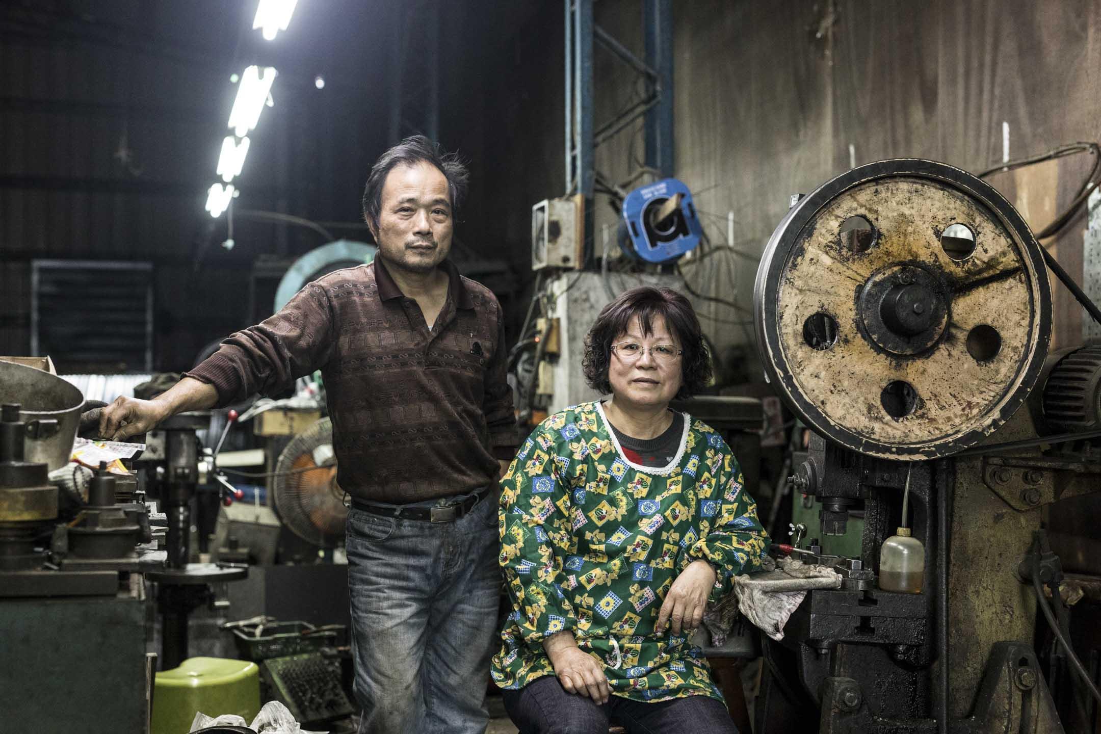 這間無名鐵皮工廠的老闆林朝山與妻子。林朝山認為,現在年輕人比較不願意待工廠,加上沖床加工業風險高,現在類似他們這種小工廠已幾乎徵不到人,多數是夫妻、家人自己做。 攝:張國耀/端傳媒