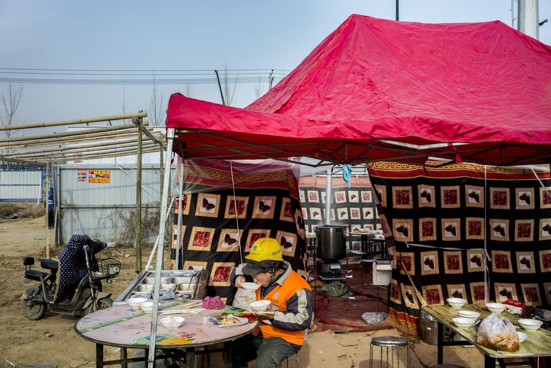 容城東部,投資8億元、佔地10萬平米的雄安市民服務中心正在熱火朝天地趕工。午飯時間,工人們都在工地外的大食堂吃飯。