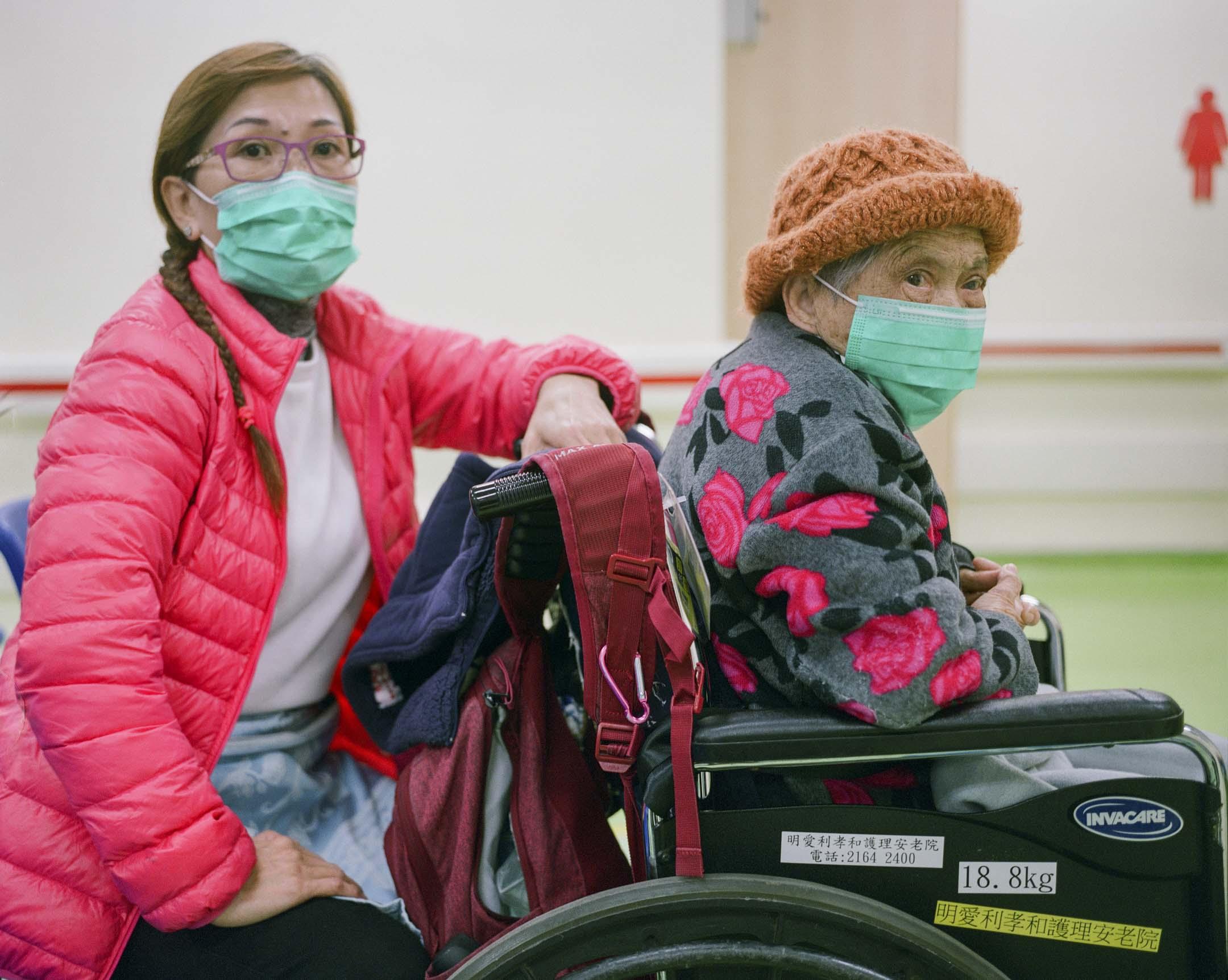 52歲的麥美𡖖陪著輪椅上91歲的陳婆婆,年輕時候的陳婆婆開朗活躍,退休後做義工,不時來威爾斯醫院義務探望病人,不少醫生和護士都認識她。後來患上各樣疾病,開始不能走路了,幾年前被家人送進了安老院。這天,麥美𡖖陪著老人,來眼科複診。 攝:林振東/端傳媒