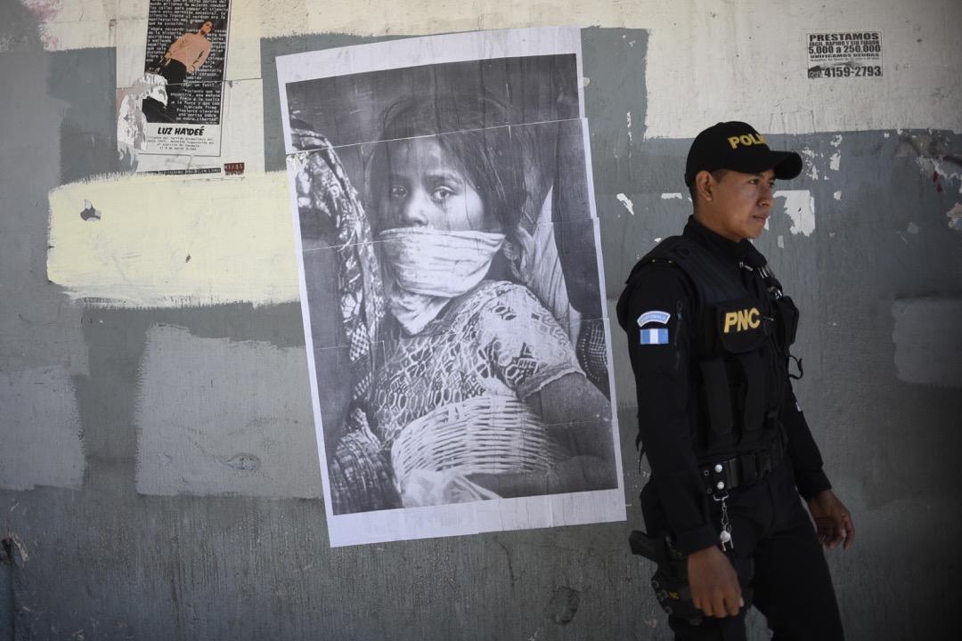 2018年3月8日,危地馬拉城,一名警員走過一張宣傳婦女節的海報。