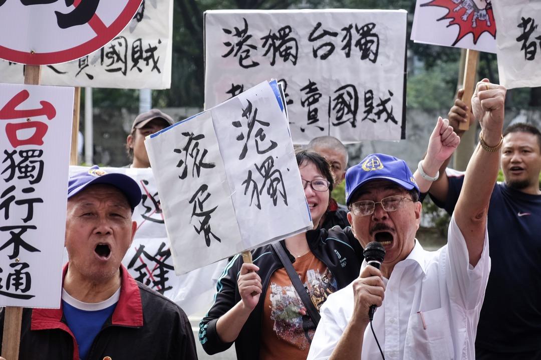 據《明報》報導,中共中央擬合併國台辦及港澳辦,分析認為此舉反映北京將「港獨」思潮提升至與「台獨」同級,並希望加強打擊。圖為2017年香港民主派立法會議員應台灣政黨時代力量邀請赴台北出席論壇,有示威者在論壇場外舉起反對港台獨立標語。 攝:Anthony Kwan / Getty Images