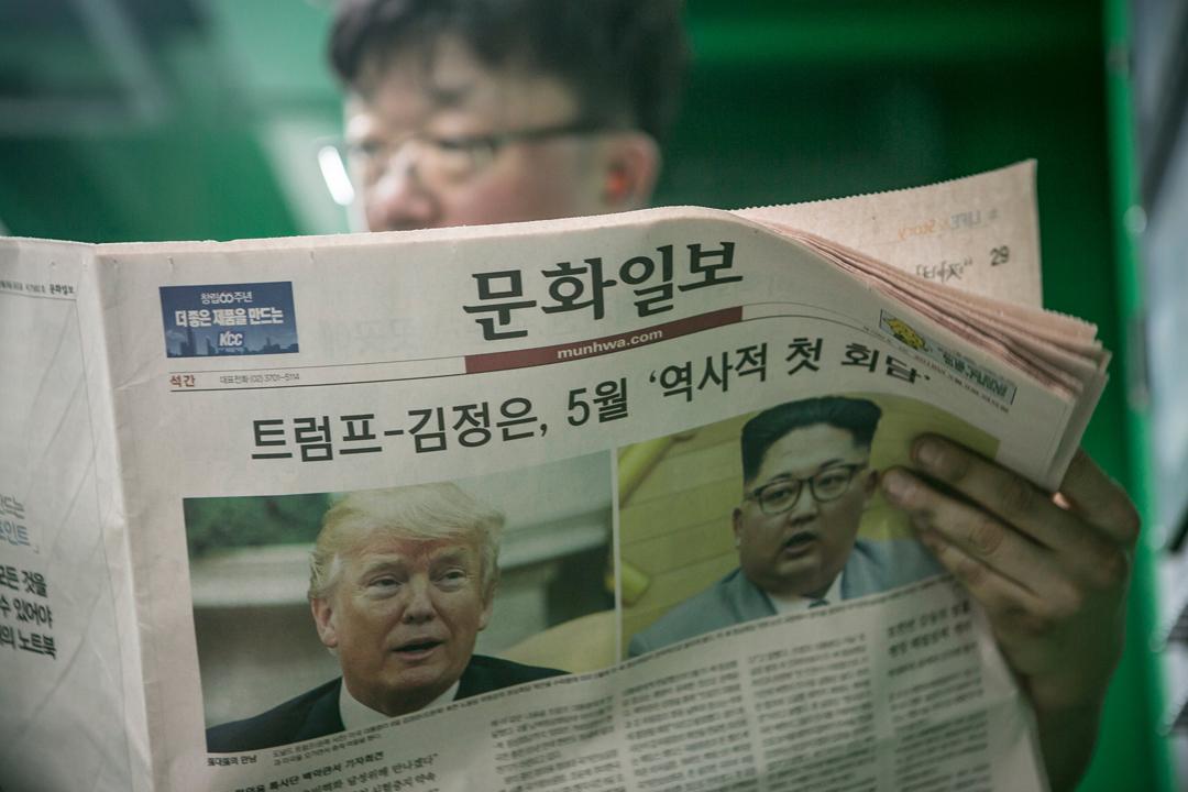 3月9日在首爾,一名男子正閱讀《文化日報》;該報以美國總統特朗普接受北韓領袖金正恩的會面邀請的消息,作為頭版報導。 攝:Jean Chung / Getty Images