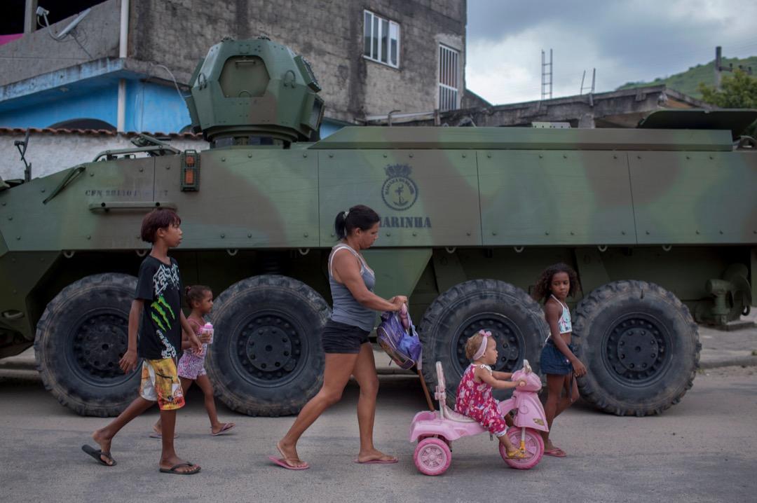 2018年3月7日,巴西里約熱內盧,武裝部隊的裝甲車駛進 Vila Kennedy 貧民窟候命行動,一名女子與孩子們在裝甲車前走過。