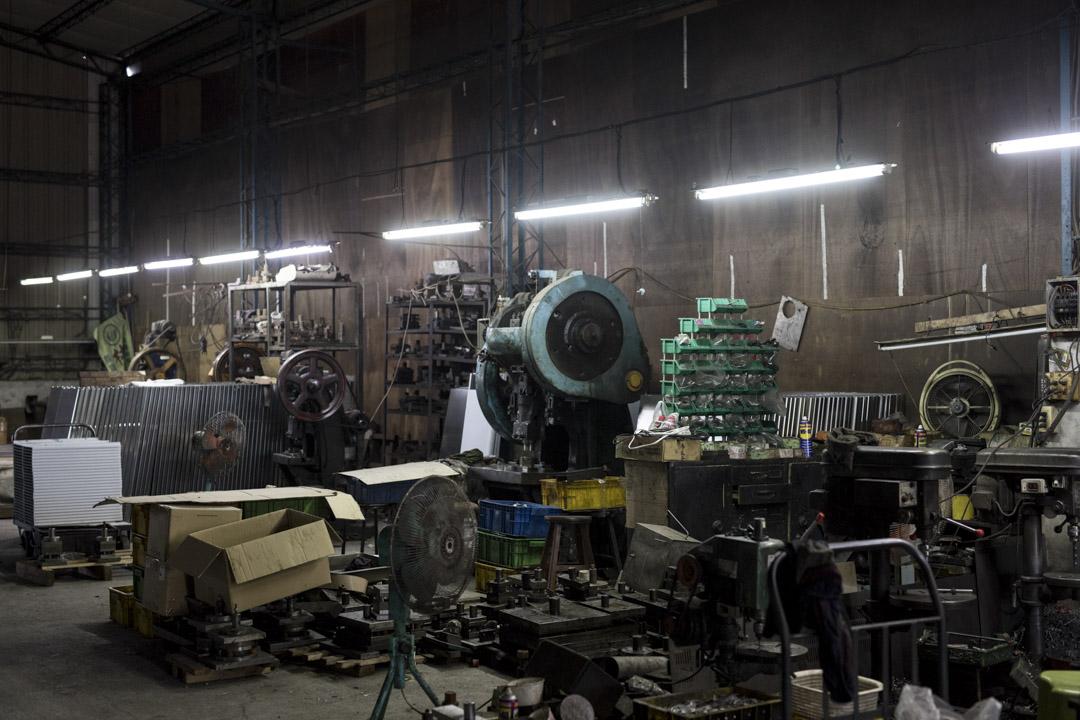 台中大里鄉間的這家小型沖床加工廠,約1.5座籃球場大小的挑高鐵皮屋內,全廠老闆加員工僅有四人,有14台沖床,加工生產諸如麵粉攪拌機零件、飲水機零配件、六角板手、套銅接頭,到各種小螺絲等各式機械零件。