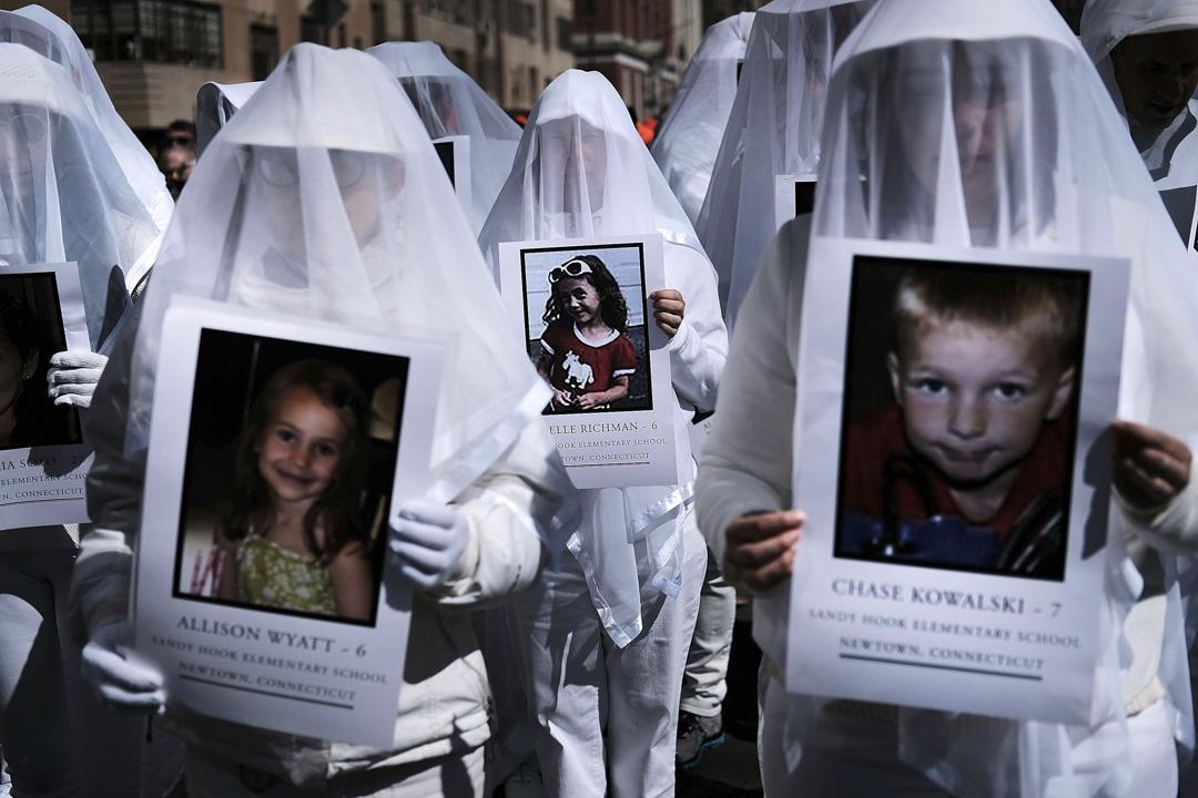 美國紐約,過千名示威者到曼克頓街頭,參與「March for Our Lives」全國性槍械管制遊行活動,其中有參與者穿起白色衣服,拿著康涅狄格州小學槍擊案中,27名死者的肖像,其中20名為7歲以下的小朋友。 攝:Spencer Platt/Getty Images
