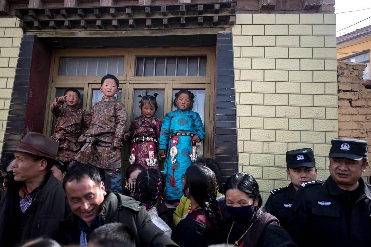 3月1日,在西藏舉行的一項儀式上,兒童和警察注視着走過的佛教僧人。
