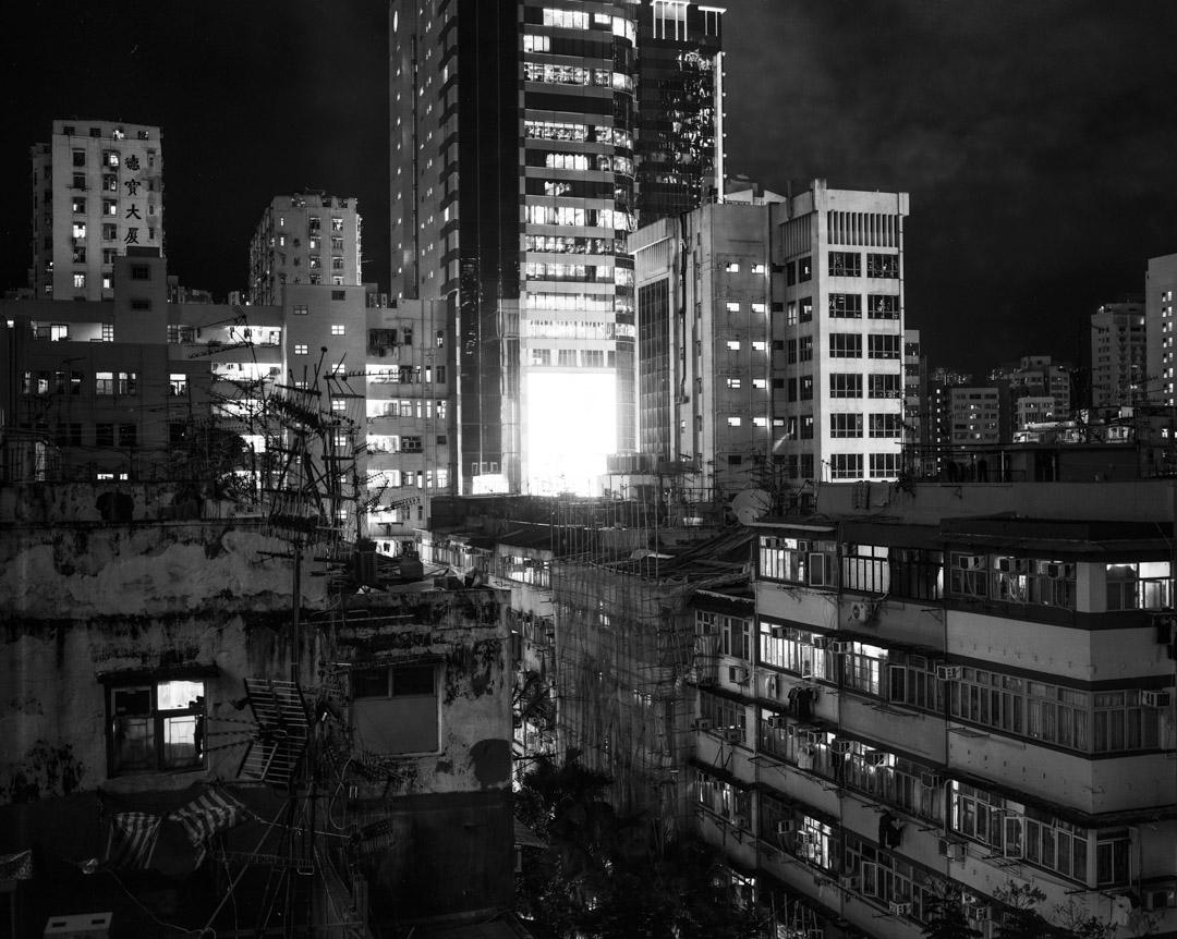 2017年7月,荃灣沙咀道一片舊樓區中豎起一幅LED大屏幕,散發耀眼的光。 攝:林振東/端傳媒