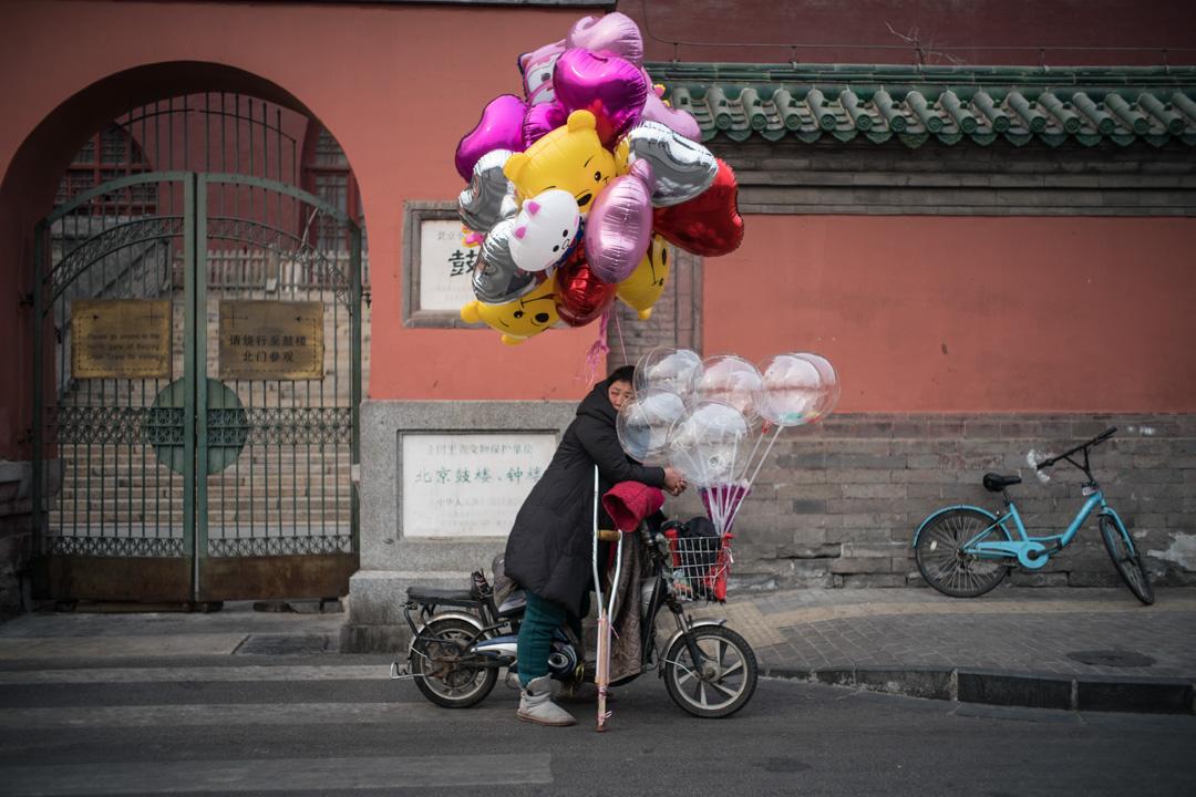 2018年3月14日,一名女子在北京的街道上賣汽球。