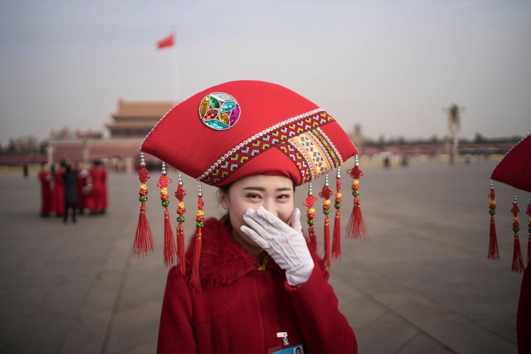 2018年3月5日,全國兩會在北京人民大會堂開幕,一名禮儀小姐在天安門廣場對著攝影師鏡頭微笑。