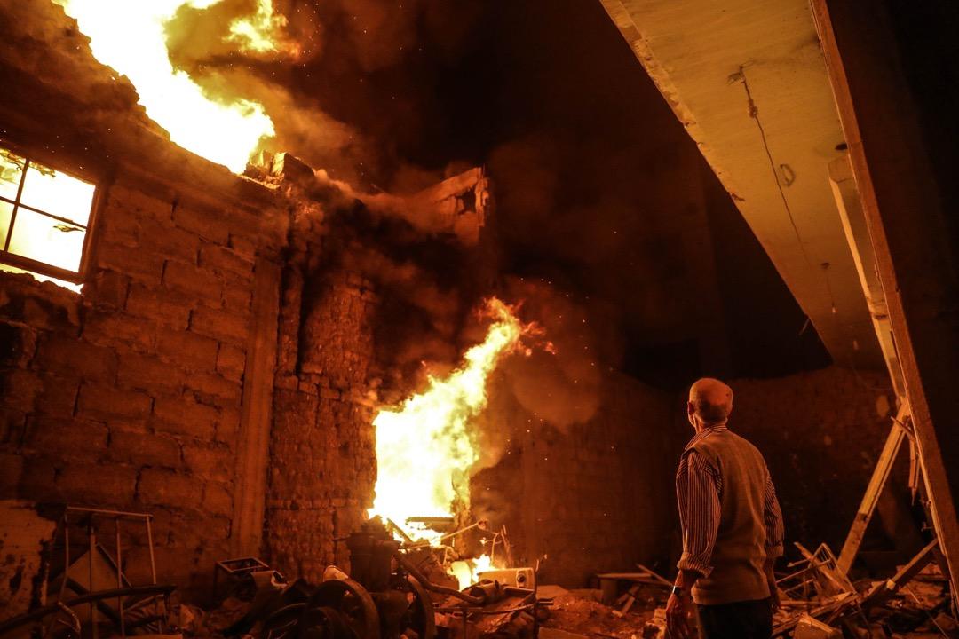 2018年3月23日,敘利亞城鎮杜馬,一名男子凝望著一棟被空襲後起火的房屋。
