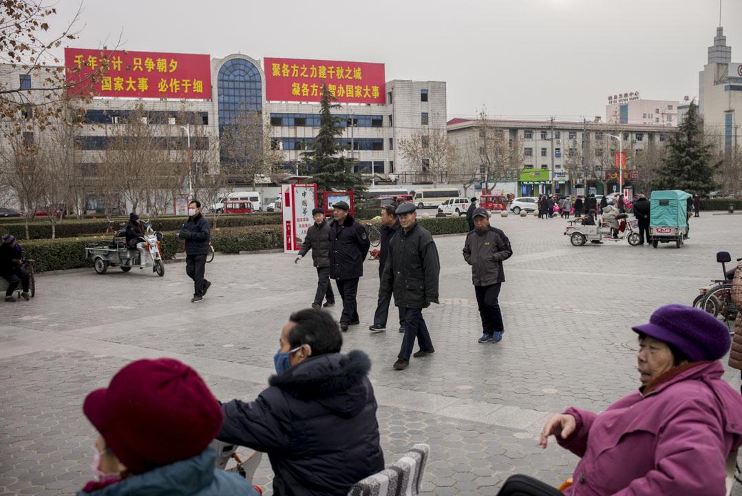市民在雄縣政府大樓前的廣場消磨時間,背後有設立河北雄安新區的大字標語。