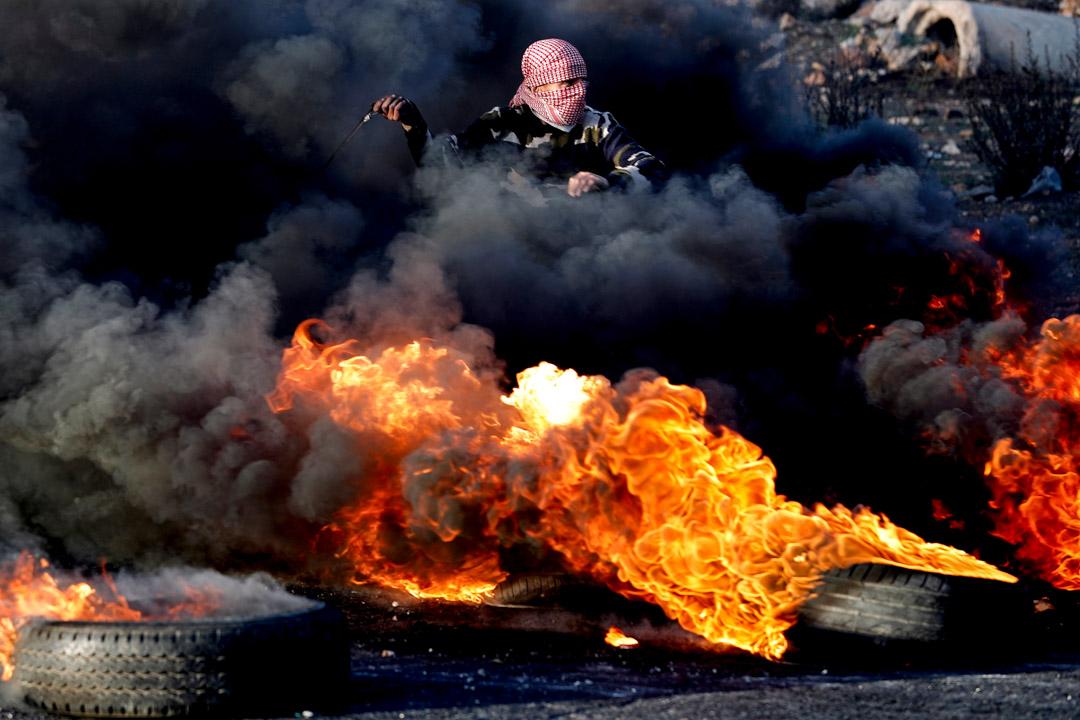 2017年12月11日,在約旦河西岸城市拉馬拉發生以巴衝突,示威者用彈弓在燃燒的輪胎煙霧中向以色列軍隊投擲石塊。