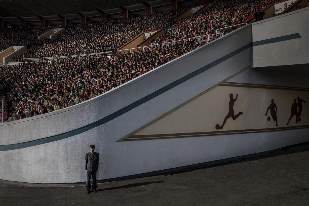 2017年4月9日,北韓平壤,觀眾在金日成體育館等候平壤馬拉松開幕,一名護衛員在場內駐守。