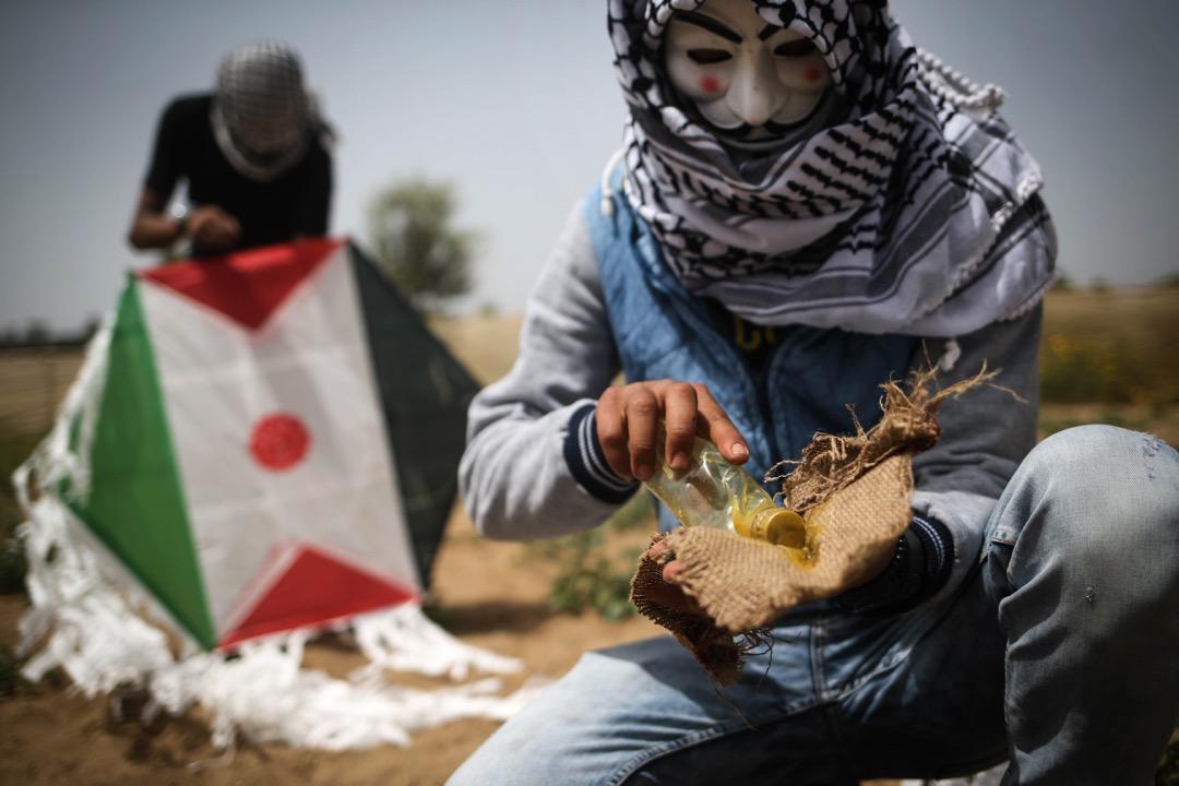 2018年4月20日,加沙地區,兩名巴勒斯坦示威者整準備用風箏將土製燃燒彈飛越以色列邊防部隊投擲到以色列領土上。由巴勒斯坦人發起,計劃持續至5月15日的「回歸大遊行(The Great March of Return)」步入第四週,巴勒斯坦示威者不斷用創新的方式攻擊以方邊防部隊。
