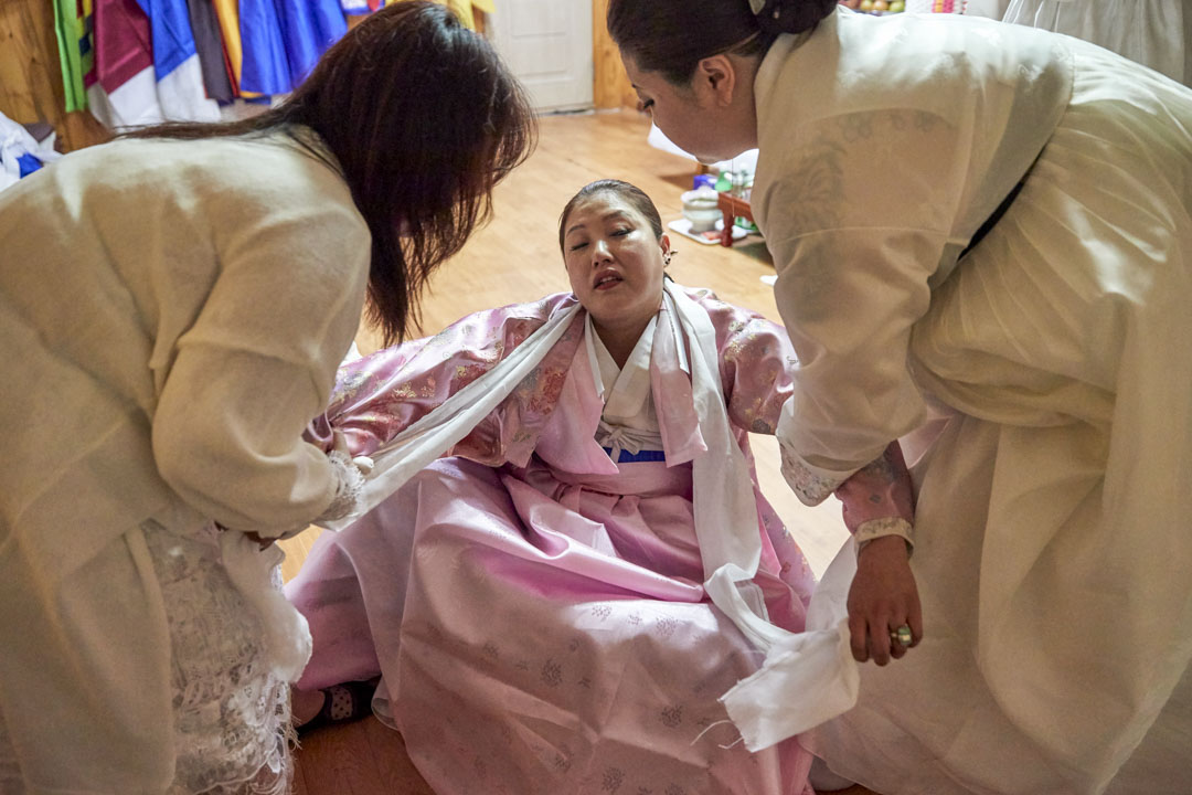 南韓京畿道,幾位薩滿巫師正在為一名信徒死去的母親作名為「羊腸」的法事,其用途在於洗滌死者的靈魂和引導死者到來世。教徒相信死者的靈魂能透過巫師的身體在此法事跟信徒對話。
