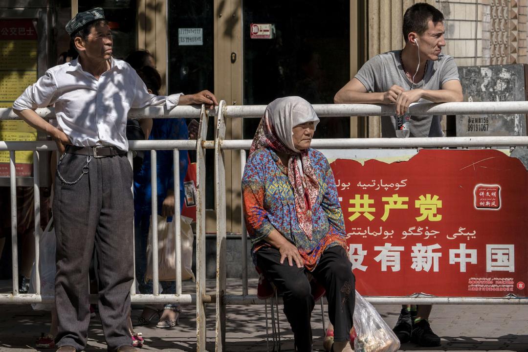 圖為2016年6月18日在新疆烏魯木齊一個巴士站,民眾依靠的欄柵掛有中共政治宣傳標語:「沒有共產黨,就沒有新中國。」 攝:Zhang Peng / Getty Images