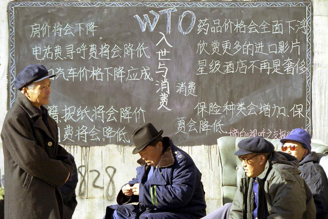 經過15年漫長的談判,中國終於在2001年12月11日正式成為世貿組織 第43名成員 。圖為當年北京市內的一塊宣傳加入世貿好處的黑板前。