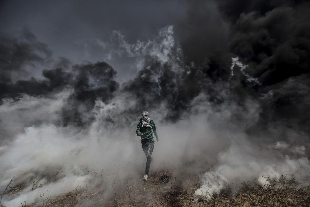 示威者用簡單布料掩面步出以軍釋放的催淚彈煙霧。
