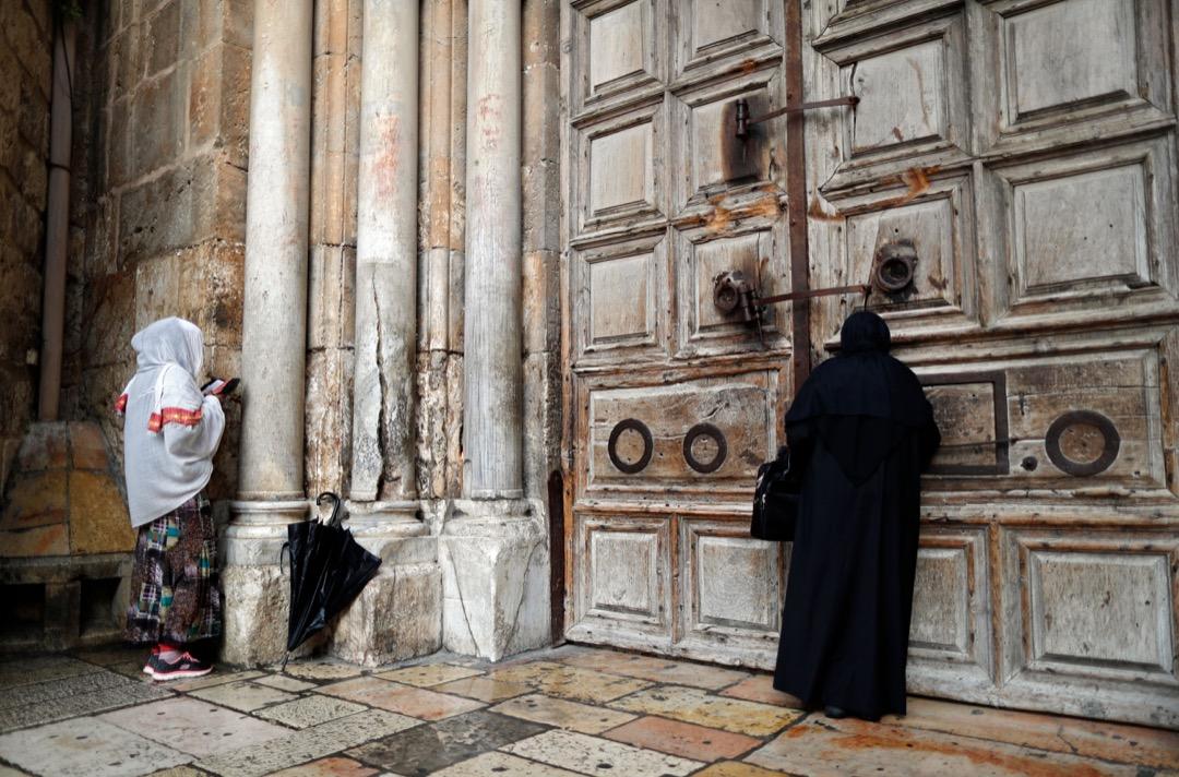 2018年2月26日,兩名基督教徒在關了門的聖墓教堂外祈禱。