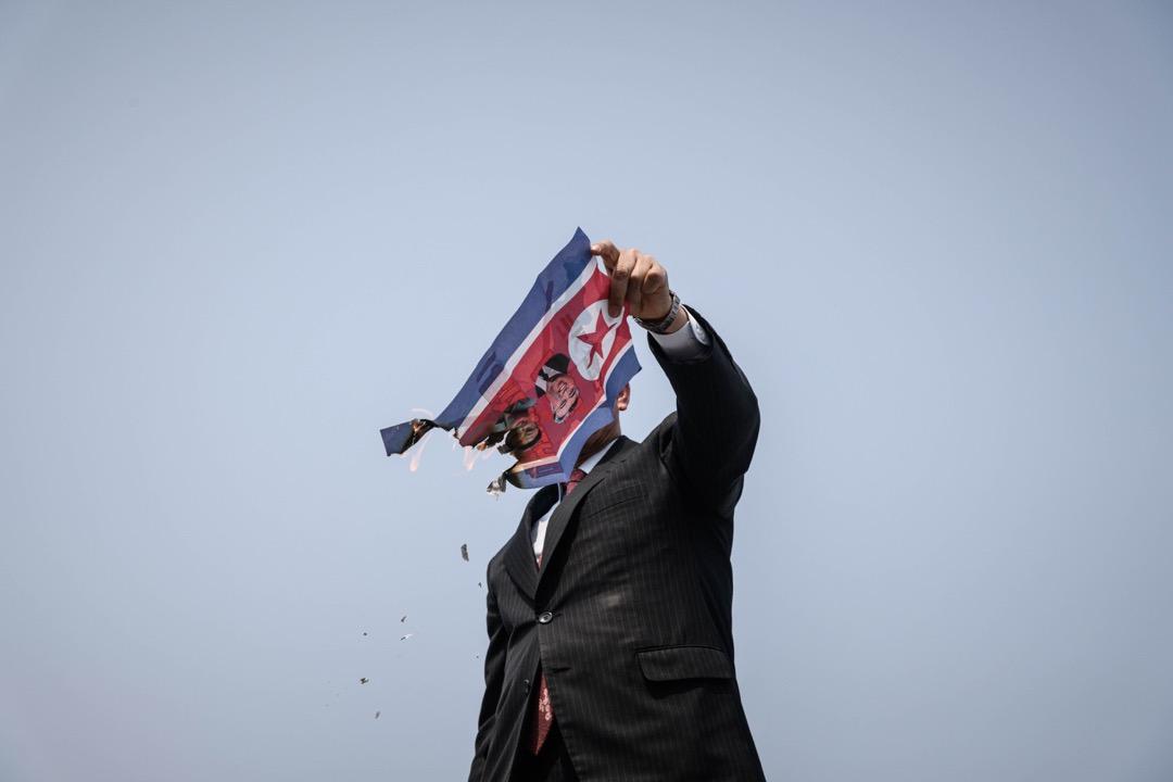 2018年4月27日,南韓坡州臨津閣和平公園通往板門店非軍事區的統一大橋檢查站,一名反北韓示威者在焚燒北韓國旗。