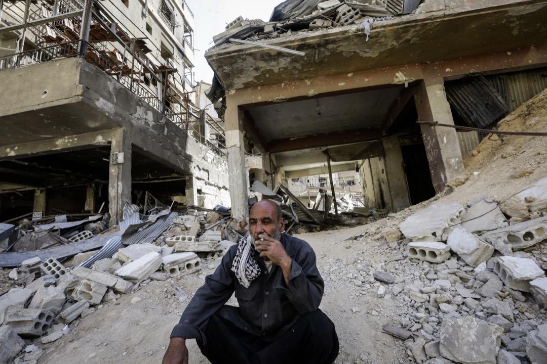 圖為2018年4月16日,美、英、法聯手空襲敘利亞的生化武器研究設施後,一名男子坐在杜馬市的一堆瓦礫旁抽菸。 攝:Louai Beshara/AFP/Getty Images