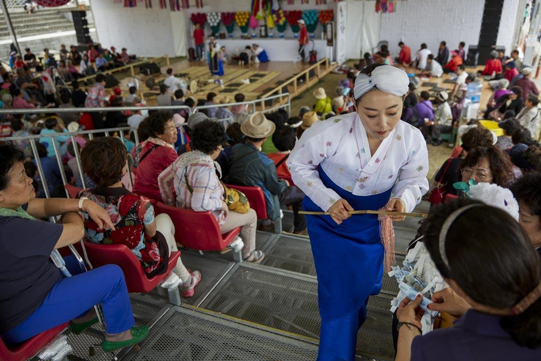 南韓江陵市,端午祭中一名年輕的薩滿巫師正在收集捐款。長達一個多月的端午祭為江陵市市民向山神祈求年年豐收的傳統習俗,於2005年成功向聯合國教科文組織將端午祭申報為非物質文化遺產。