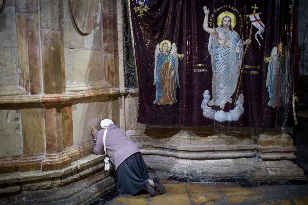 2018年3月29日,聖墓教堂舉行彌撒期間,一名女士在教堂內的耶穌之墓前跪拜祈禱。