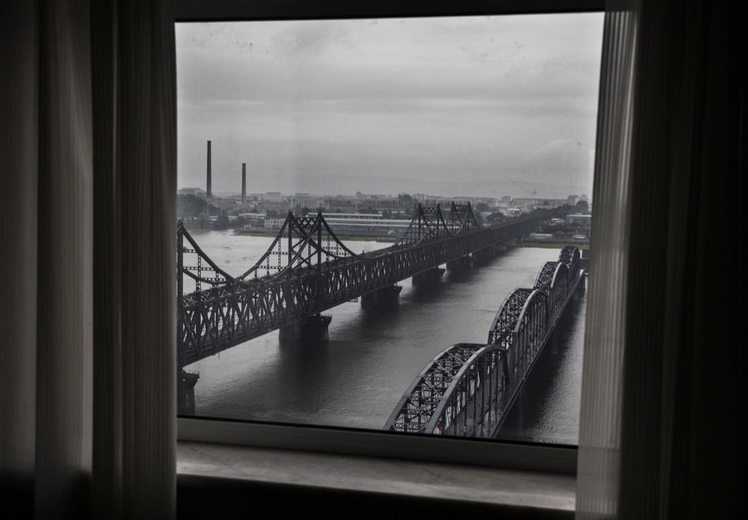 綠皮黃線的車廂停靠月台,側身標示丹東直達平壤。金正恩訪中過後一週,我們坐著相同外型,內裝完全不同的列車進入北韓。列車駛過連接中國和朝鮮兩國的鴨綠江大橋,相機鏡頭還聚焦在右側的斷橋遺跡。