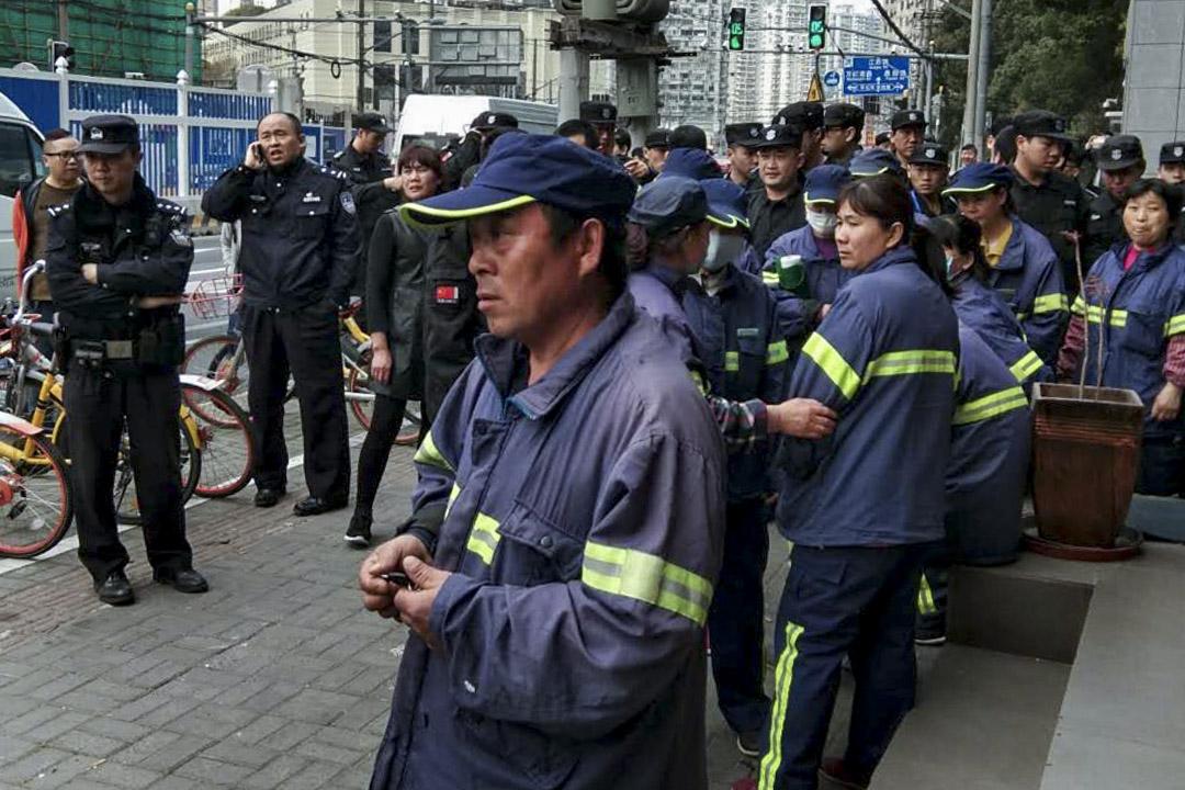 上海市長寧區環衛工人罷工現場。長寧區的環衞工並不屬於政府管轄,而環衞工作被外包給三家公司,而這三家公司又與另一家公司簽訂了勞務派遣合同,由此形成了一個複雜的利益鏈條,從而規避了一系列風險。 圖:網上圖片
