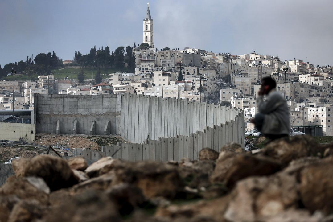 「一國方案」依然很難成為解決巴以問題的正式選項。然而,若「兩國方案」的謊言被進一步戳破,積重難返的「一國」現狀下,巴勒斯坦人的新一輪鬥爭將隨時有可能為巴以地區帶來又一場災難。圖為一名巴勒斯坦男子坐在以巴之間的隔離牆前。 攝:Thomas Coex/AFP/Getty Images
