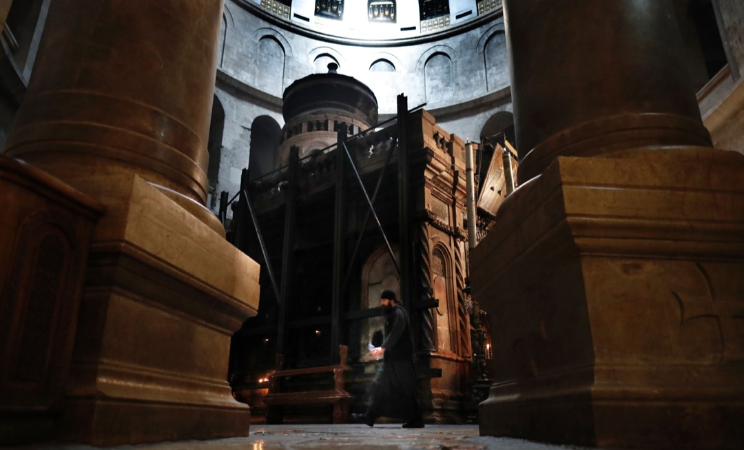 2016年3月23日,一名希臘牧師走過聖墓教堂圓形大廳內的耶穌之墓。