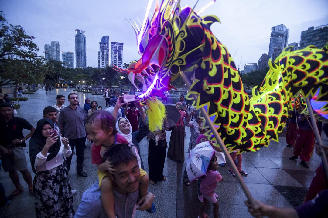 740萬「馬來西亞華人」裏,真正熟知自己群體歷史的,恐怕是少數中的少數。 他們對政治歷史文化語言民族的看法南轅北轍,缺乏共同的認知和理解,使得他們要展開任何有深度的公共議題討論,都非常困難。圖為馬來西亞華人於農曆新年期間在吉隆坡一家購物中心外觀看舞龍。 攝:Alexandra Radu/Anadolu Agency/Getty Images