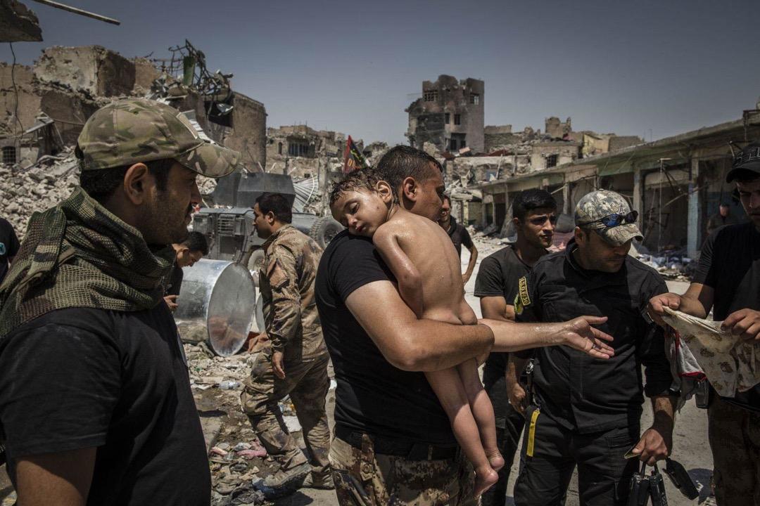 2017年7月12日,敘利亞摩蘇爾舊城區,伊拉克特種部隊士兵從一名懷疑是恐怖組織「伊斯蘭國」成員的人手中接過一名沒穿衣服的男童。