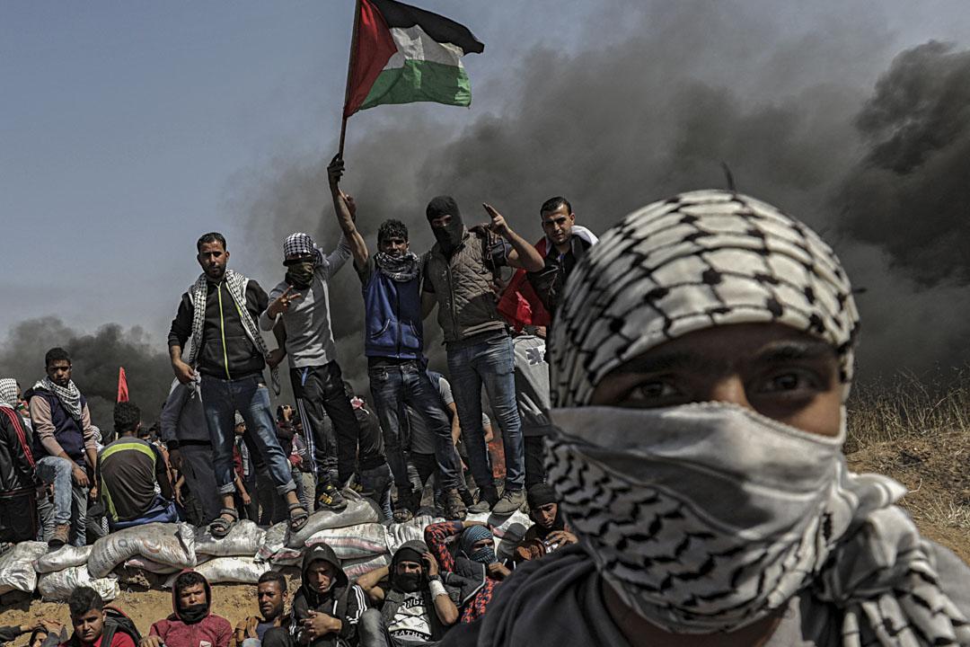 示威者在衝突期間高舉巴勒斯坦國旗。