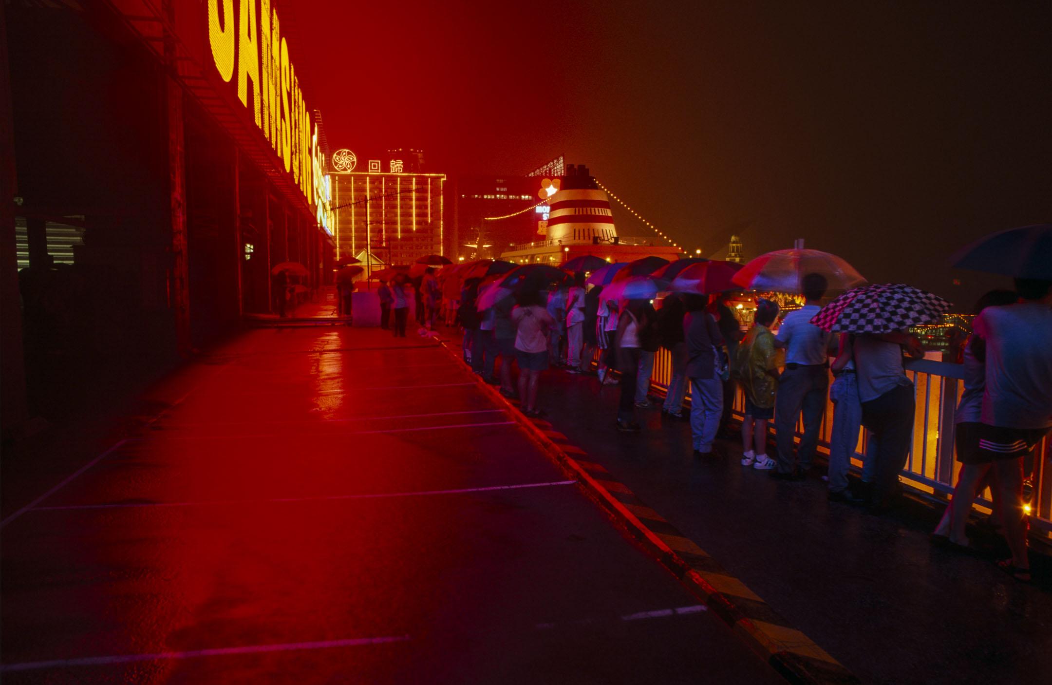 中史課程改革中首次加入了「香港史」原素,以中國歷史發展為主軸,論及香港。有評論認為將香港史放在中國史主軸之中學習,削弱了香港為本位的視角,讓香港發展淪為中國歷史的附屬品。圖為1997年的香港海運碼頭,市民冒雨迎接回歸的歷史時刻。 攝:Pictures Ltd./Corbis via Getty Images
