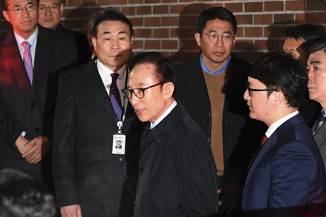 南韓檢察部門今天正式以涉嫌收受賄賂、逃稅、濫用職權等共16項罪名,對前總統李明博提出起訴。圖為上月22日,檢方獲法庭批准後,前往李明博私宅將他拘捕。 攝:Jung Yeon-Je / Getty Images