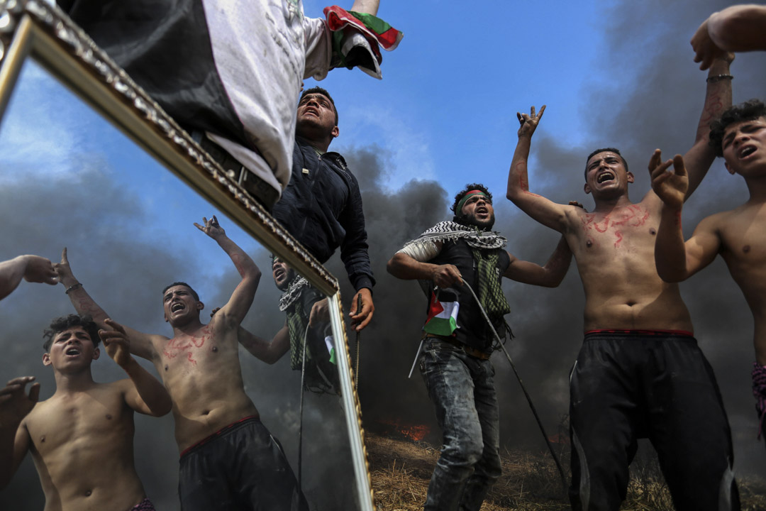 """2018年4月2日,巴勒斯坦民眾於加沙地帶持續""""回歸大遊行""""示威,示威者手持鏡子在以巴邊境與以色列軍隊發生激烈衝突。"""