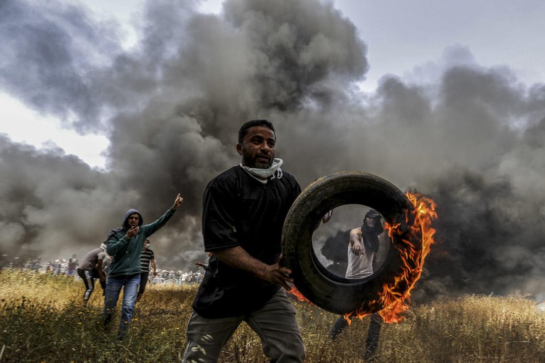示威者手持焚燒中的車胎。
