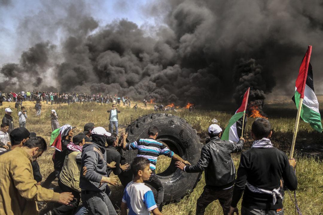示威者準備焚燒車胎製造黑煙遮擋以色列狙擊手的視線。