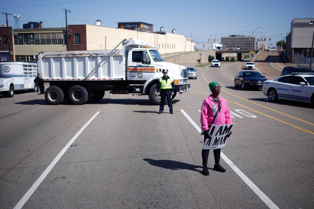 2018年4月4日,美國田納西州孟菲斯,有活動紀念馬丁·路德·金遇刺50週年,一名參加者在路中心拿著寫著「I Am a Man」字句的紙牌,重演馬丁·路德·金遇刺時正帶領的清潔工人罷工運動的情況。