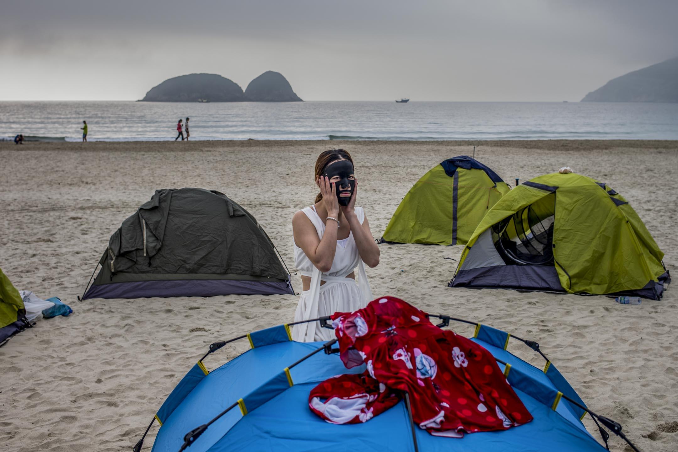 2018年5月1日清晨,不少內地客在鹹田灣露營,有旅客正在敷面膜。近年有大量內地團以平價招徠,到自然景色優美的西灣及鹹田灣舉辦生態遊,費用包括交通及住宿營具。 攝:林振東/端傳媒