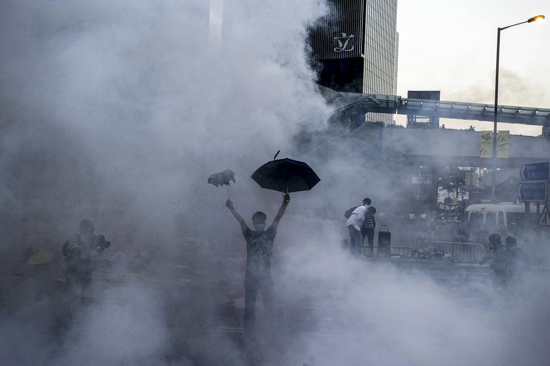 9月28日凌晨,戴耀廷宣布「佔領中環」正式啟動。當日上午警方封鎖政府總部,導致前往添馬艦支援佔領人士的市民被堵塞在海富中心附近,因而在下午衝出夏慤道等主幹道;黃昏警方展開大規模驅散行動,施放87顆催淚彈,令民憤進一步爆發,及引起國際關注。 攝:Xaume Olleros/AFP/Getty Images