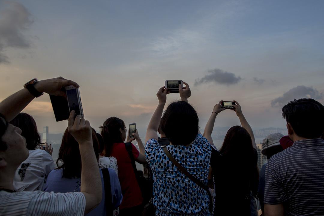 2018年5月1日傍晚,不少內地遊客到山頂觀看維港黃昏的景色。