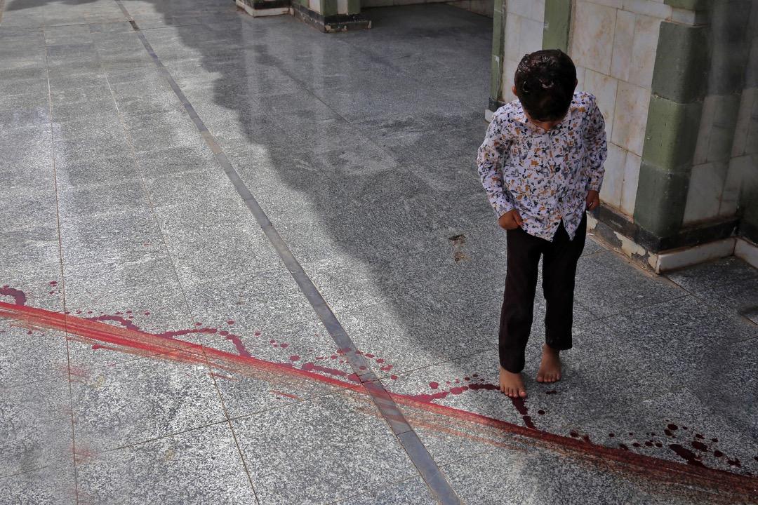2018年5月14日,也門城市塔伊茲,一名男孩凝望著地上的血痕。較早前市內最大的清真寺的領袖 Mohammed Al-Zabhani被刺殺,在地上留下血跡。